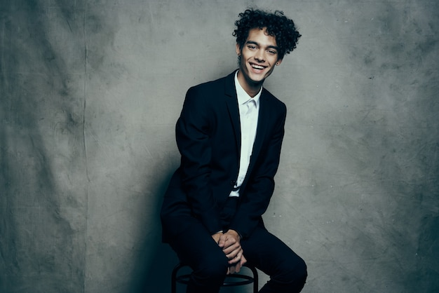 Business man in a suit curly hair sitting on a chair fashion modern style