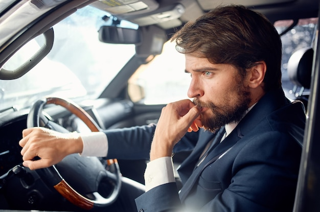 Business man in suit driving a car trip luxury road.