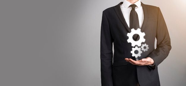 Business man in suit holding metal gears and cogwheels mechanism representing interaction teamwork concept,hand hold group of virtual cog gears wheel