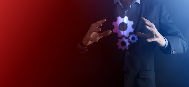 Business man in suit holding metal gears and cogwheels mechanism representing interaction teamwork concept,hand hold group of virtual cog gears wheel.