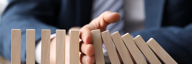 Business man in suit holding with hand falling sequence of wooden blocks closeup