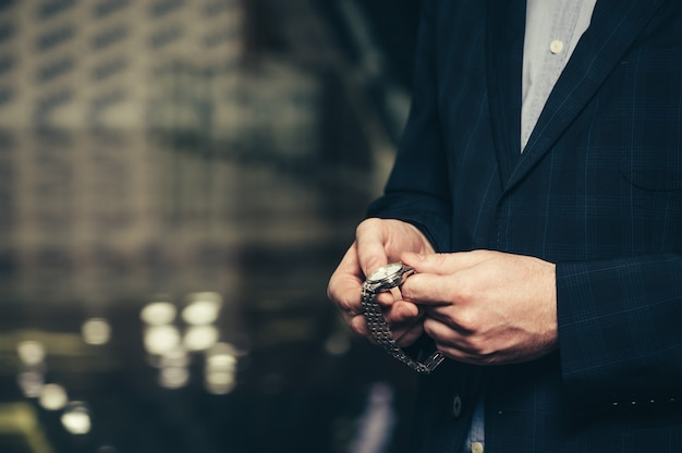 A business man in a suit sets up time in a wrist watch