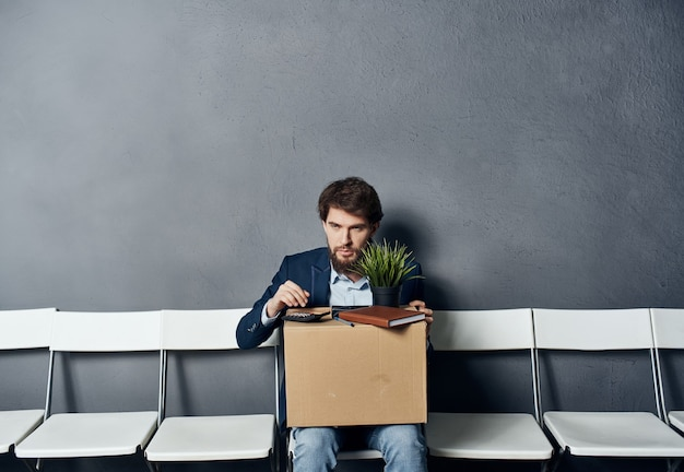 Business man in a suit sits on chairs a box with sacking things