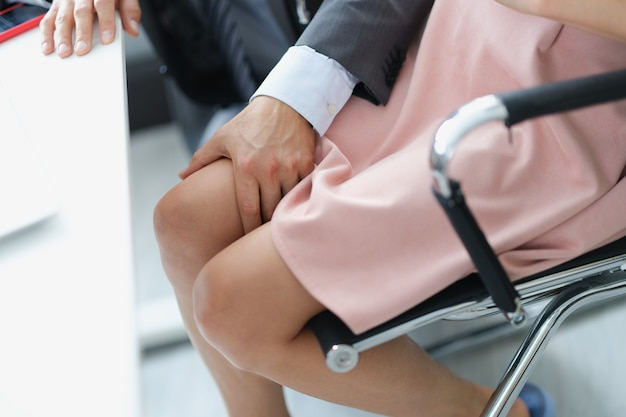 Business man in suit touching knee of woman at work closeup