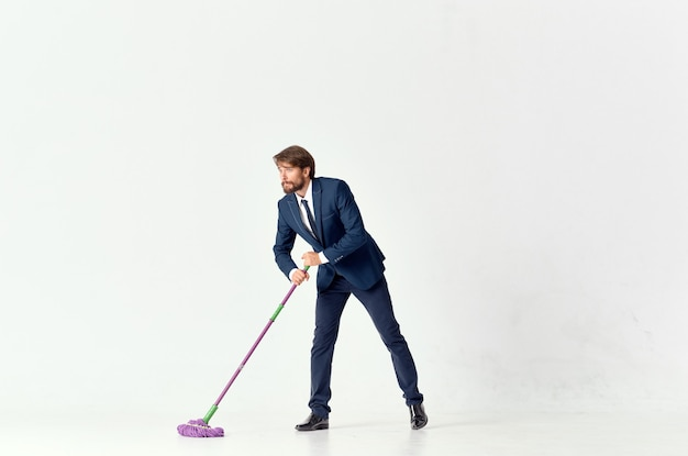 Business man in a suit washes the floors with a mop manager