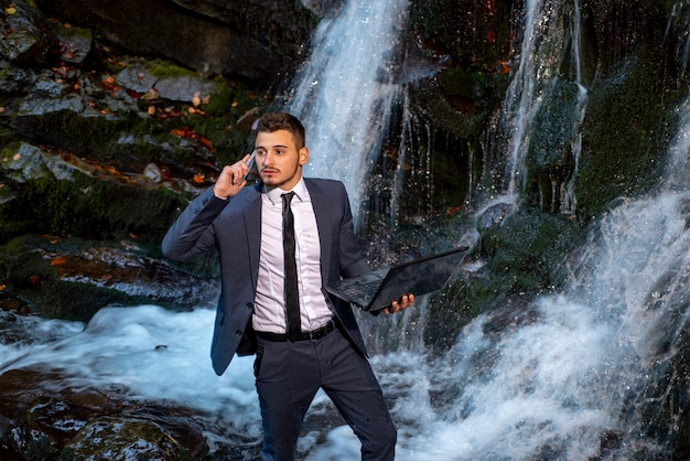 Business man in suit with laptop at waterfall background. waterproof device concept. telework businessman.
