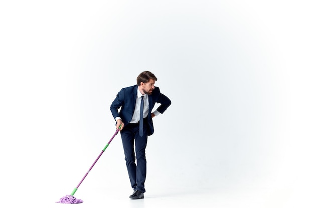 Business man in a suit with a mop in his hands cleaning service