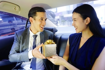 Business man surprise the lover on car with gift box. happy family couple surprising each