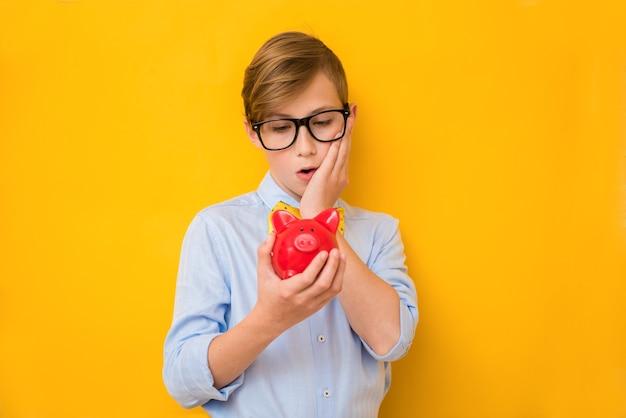Бизнесмен. удивленный мальчик-подросток держит красный копилку. бизнес-концепция. экономия денег концепция. банковская реклама. копилка. финансовый банкрот