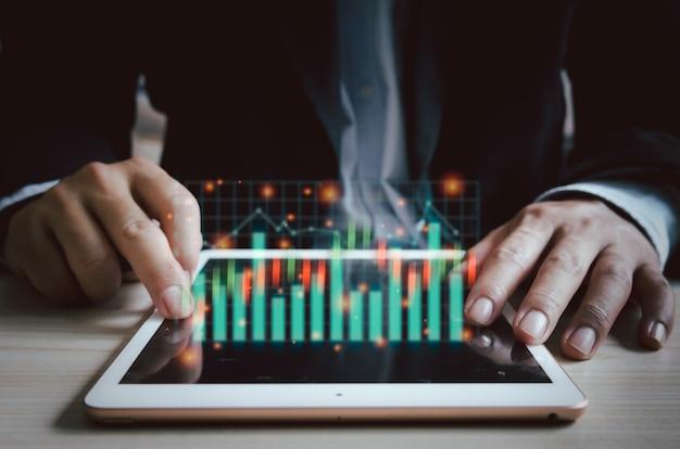 График и диаграммы запаса виртуального экрана планшета делового человека. финансы и инвестиционная концепция делового цифрового маркетинга.