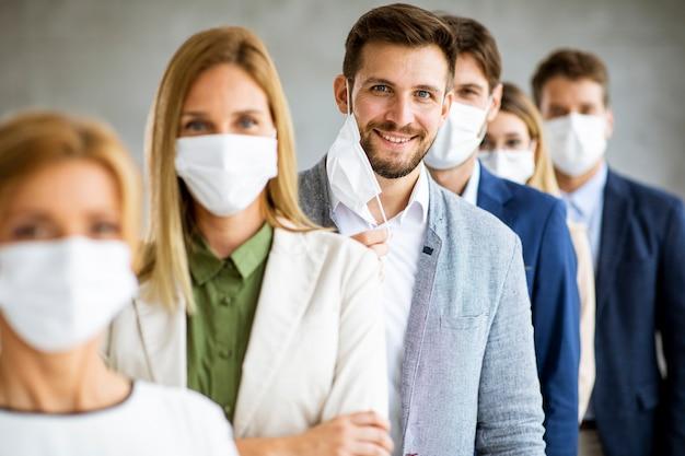 Деловой человек снимает защитную маску на лице и смотрит в камеру с членами своей команды, стоящими в очереди в офисе
