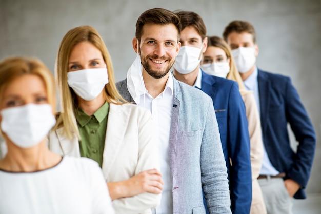 Деловой человек снимает защитную маску для лица с членами своей команды, стоящими в очереди в офисе