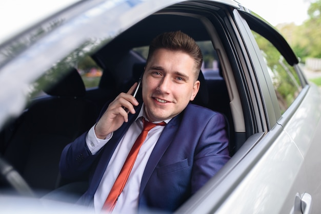 Business man talking on mobile phone in car.