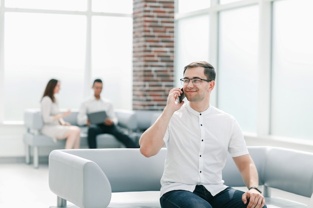 Business man talking on a mobile phone in the lobby of the business center. business concept