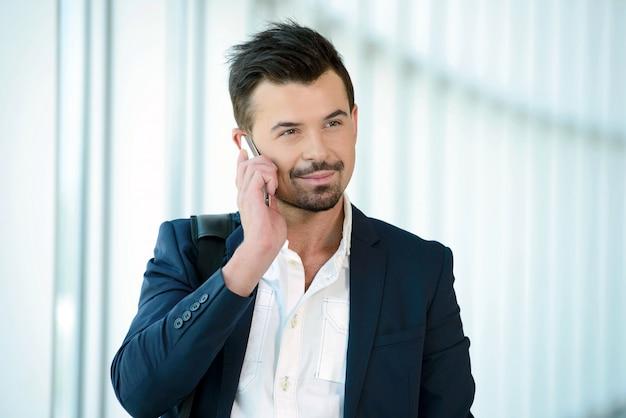 ビジネスの男性が電話で話していると空港の中を歩きます。