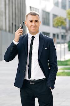 Деловой человек разговаривает по смартфону на улице