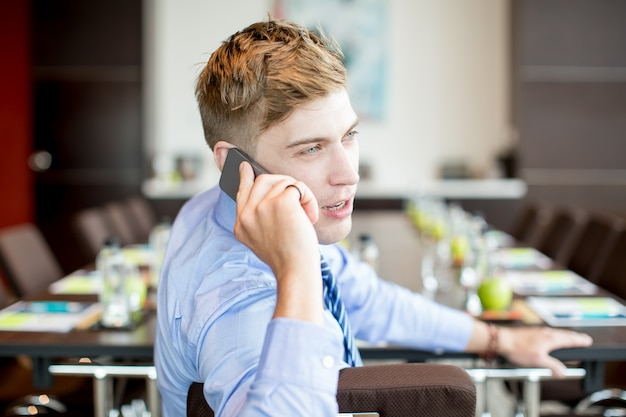 Business man talking on phone at conference table