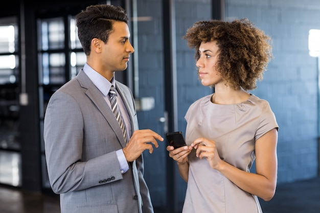 Business man talking to young woman holding mobile phone in office