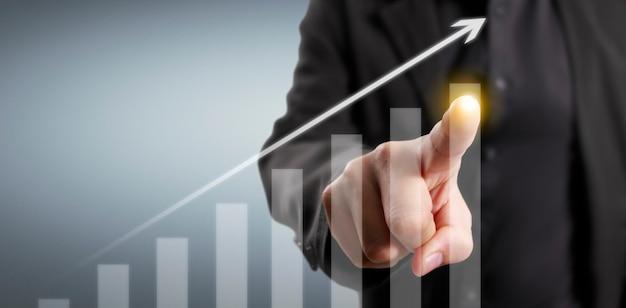 上向きの矢印とグラフのデジタルデザインに触れるビジネスマン