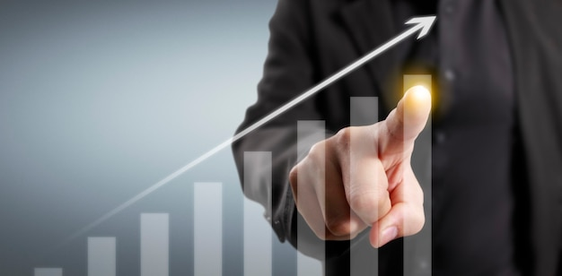 Business man touching a digital design of an arrow and a graph gowing up