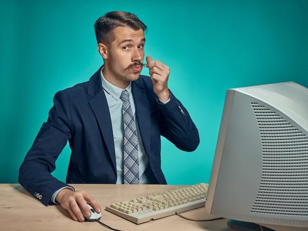 Uomo di affari che tocca i suoi baffi seduto alla scrivania davanti al computer