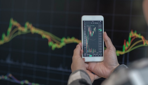 Business man trader investor analyst using mobile phone app analytics for cryptocurrency financial stock market analysis analyze graph trading data index investment growth chart on smartphone screen.