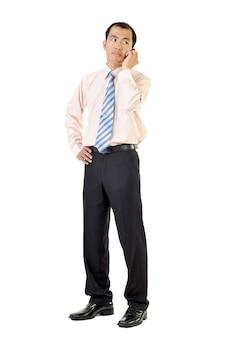 Деловой человек использует сотовый телефон, слушая и стоя на белом фоне.
