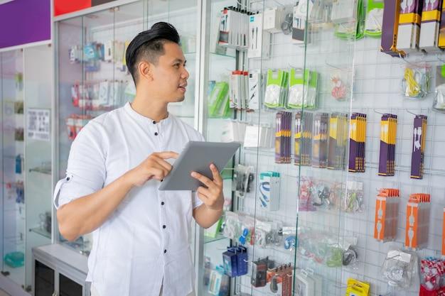 ガラスの陳列ケースに付属品のタイトな在庫を持つタブレットを使用してビジネスマン