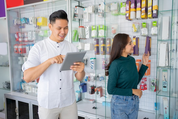 携帯電話のアクセサリー製品を選択する女性とタブレットを使用してビジネスマン