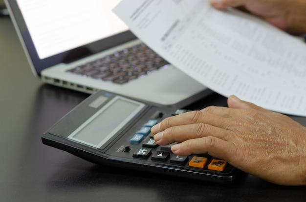 デスクで電卓を使用してビジネスマン。ビジネスファイナンス、税金、投資の概念。