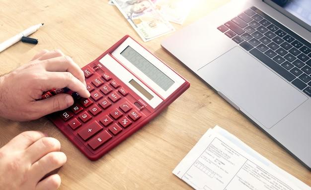 Деловой человек с помощью калькулятора для расчета налогов