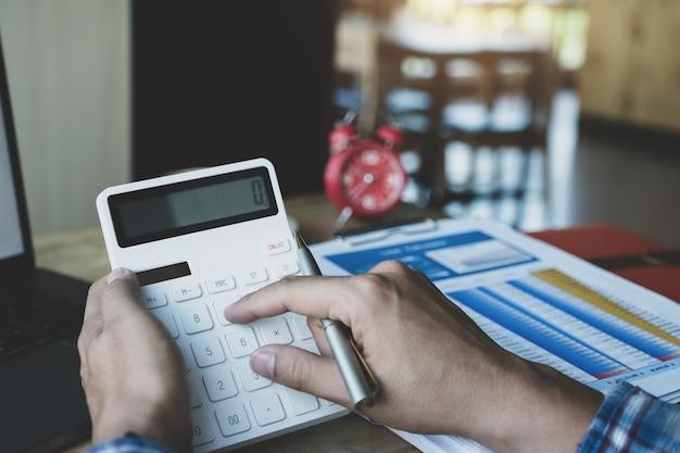 Бизнесмен используя калькулятор для того чтобы пересмотреть годовой баланс с ручкой удерживания и используя портативный компьютер