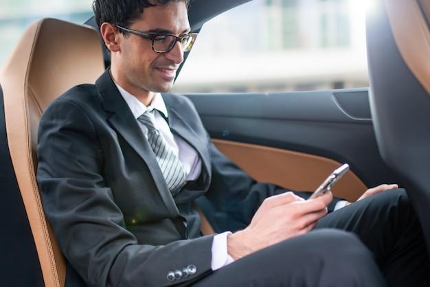 자동차 뒷좌석에서 스마트폰을 사용하는 사업가