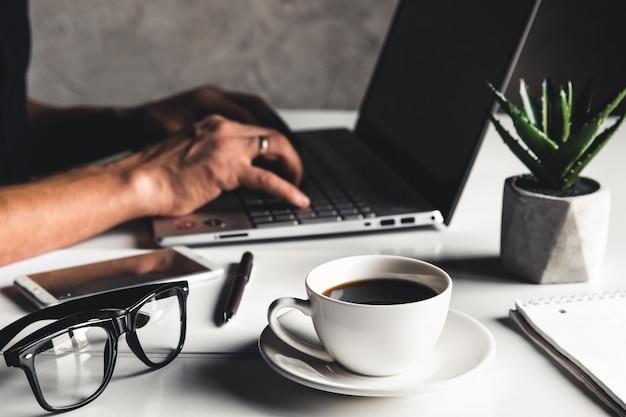 ノートパソコンとノートパソコンのペングラスとホットコーヒーのカップでラップトップキーボードで手入力を使用してビジネスマン