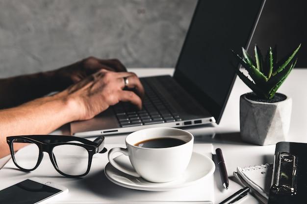 노트북 컴퓨터와 노트북 펜 안경과 뜨거운 커피 한잔 노트북 키보드에 입력하는 손을 사용하는 비즈니스 남자