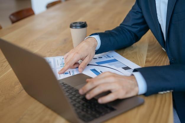 랩톱 컴퓨터를 사용하는 비즈니스 남자, 입력, 정보 검색, 현대 사무실에서 문서 작업, 손에 집중