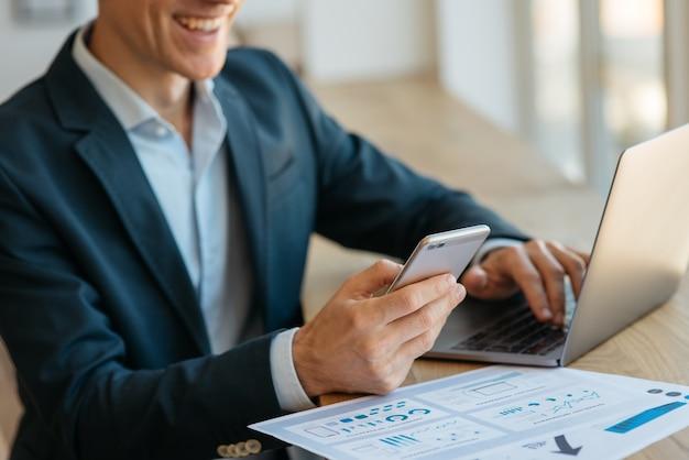オフィスでオンラインで働く携帯電話を持つラップトップを使用するビジネスマン