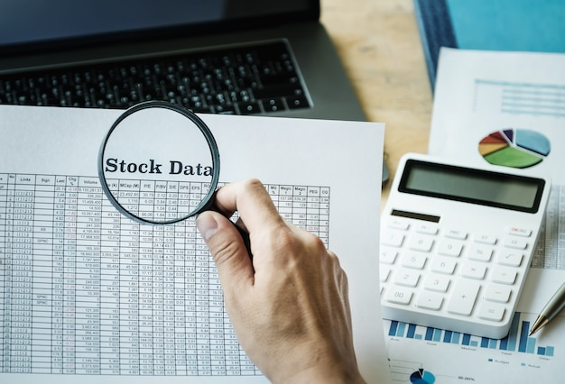 Business man using magnifying to review balance sheet