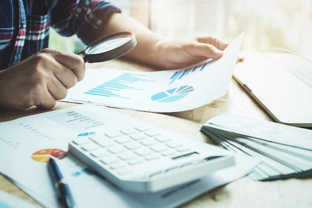계산기와 노트북 컴퓨터를 사용하여 연간 대차 대조표를 검토 돋보기를 사용하여 비즈니스 사람
