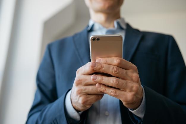 携帯電話、コミュニケーション、オンラインでの作業、手に焦点を当てるビジネスマン