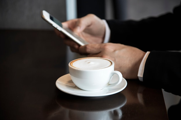 Business man using mobile phone while drinking coffee in coffee shop