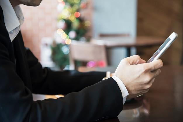 コーヒーショップでコーヒーを飲みながら携帯電話を使用してビジネス男