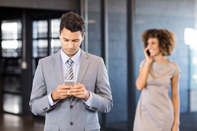 Business man using mobile phone with a smiling woman