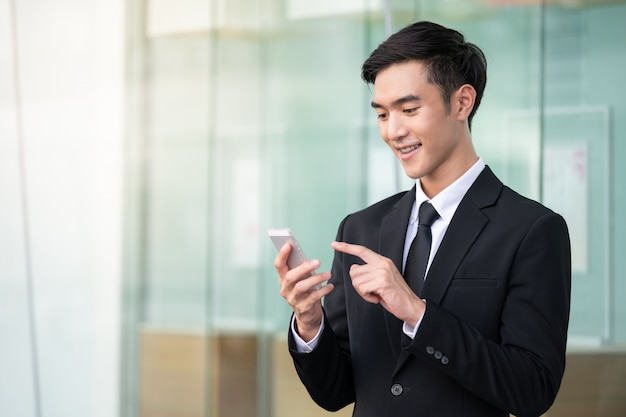 Business man using mobile phone for work or shopping online.