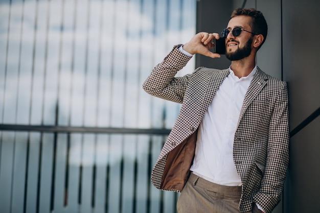 Деловой человек с помощью телефона за пределами офисного центра