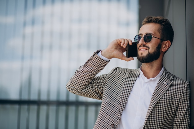 オフィスセンターの外の電話を使用してビジネスの男性