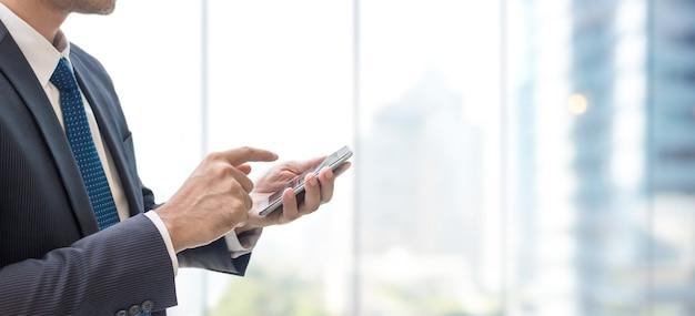 도시 배경 및 복사 공간 창에 스마트 휴대 전화를 사용 하여 비즈니스 사람.