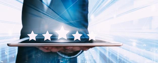 고객 서비스 비율을 제공하기 위해 5 별 아이콘 그래픽으로 태블릿 응용 프로그램을 사용하는 비즈니스 남자