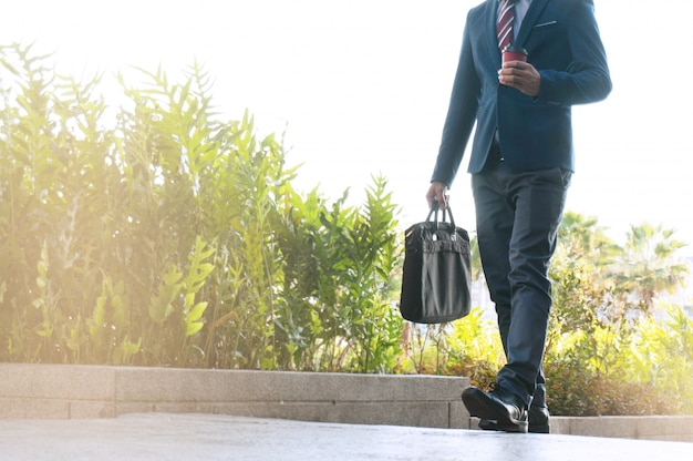 Business man walking to office with holding a briefcase