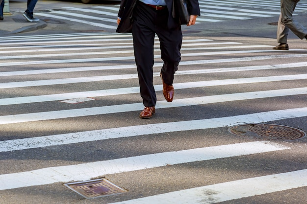 Business man walks on a pedestrian crossing